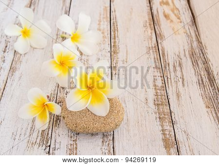 Tropical Plumeria And Stone Therapy On Wooden Table
