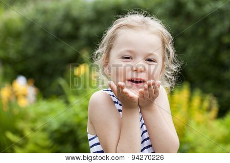 Happy little Girl Blowing a Kiss, on summer park background