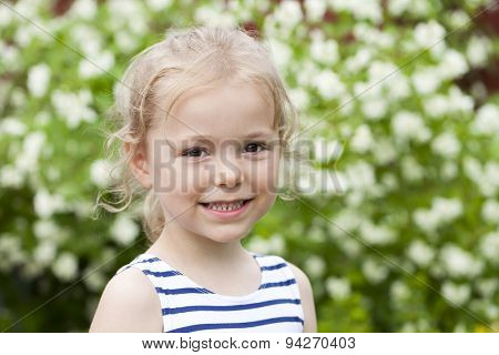 Portrait of beautiful happy little girl, against background of summer park