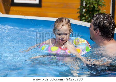 Little girl in bikini bathing in the pool with his father