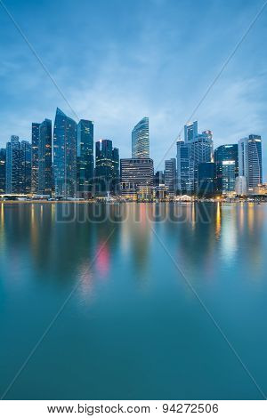 Singapores business district at twilight with water reflection