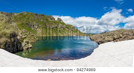 Small Mountain Lake With Snow To The Edge