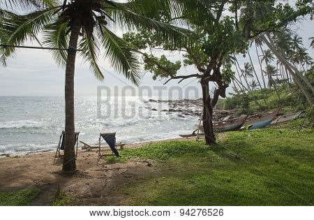 Beach with lounge chair and wood boats on sandy beach