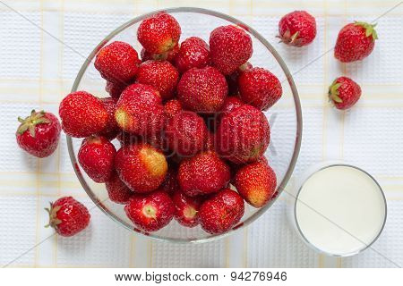 Ripe strawberries in the glass bowl with glass of milk