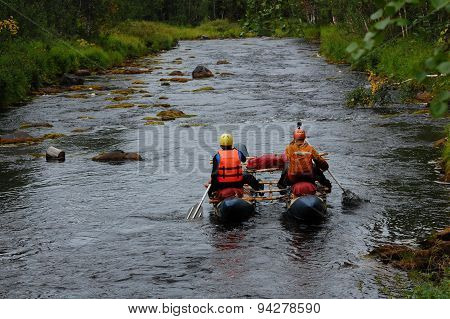Two men on a catamaran raft down the taiga river.