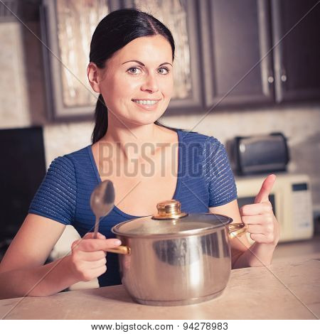 Young Housewife Cooks Food In Kitchen