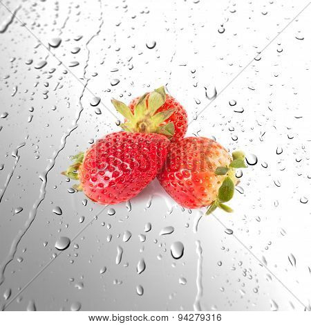 Fresh juicy strawberries on wet surfaces or Water drops background