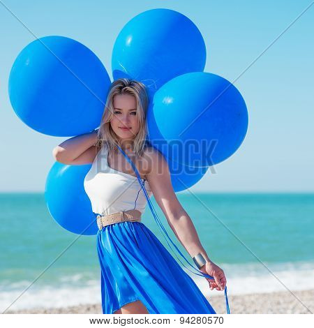 Woman Holding Bunch Of  Air Balloons At The Beach