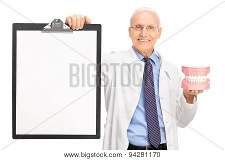 Studio shot of a mature dentist holding a denture and a clipboard with a blank paper on it isolated on white background