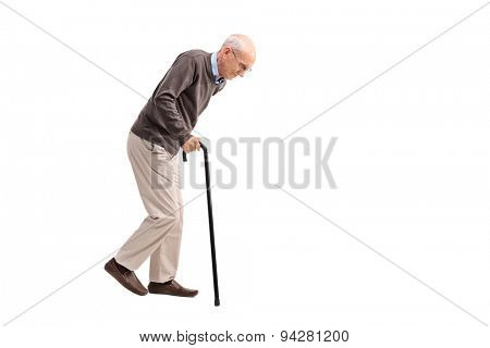 Studio shot of an exhausted old man walking with a cane isolated on white background