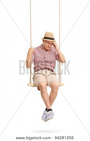 Vertical shot of a depressed senior man sitting on a swing and remembering something isolated on white background