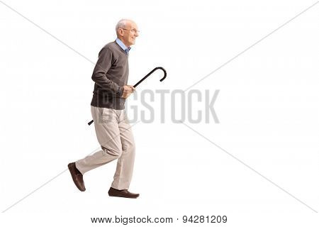 Full length portrait of a joyful senior gentleman carrying a cane in his hand and running isolated on white background