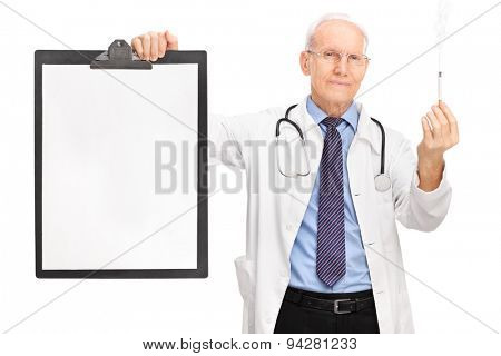 Studio shot of a mature doctor holding a burning cigarette and a clipboard with a blank paper on it isolated on white background