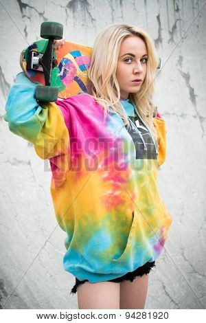 Blond skater girl holding skateboard