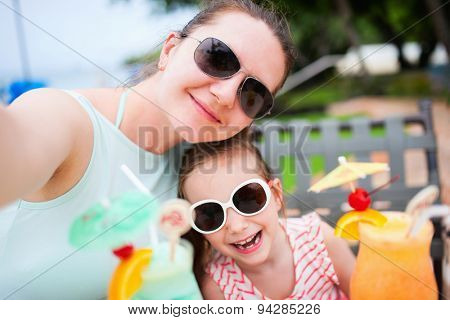 Happy mother and her adorable little daughter at outdoors cafe taking selfie while drinking tropical juice