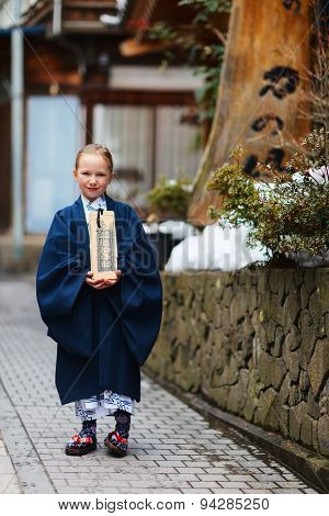 Adorable little girl kimono at street of resort town in Japan going to public hot spring spa. Translation of the text on wooden plate: passport for round bath visit to protect you from bad luck.