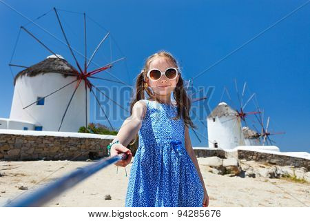 Cute little girl taking selfie with a stick in front of windmills at popular tourist area on Mykonos island, Greece