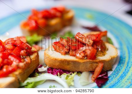 Fresh homemade crispy Italian antipasto bruschetta topped with tomato, garlic and basil