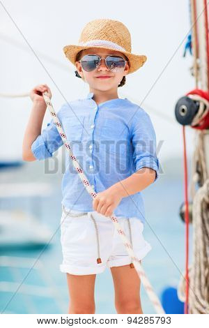 Adorable little girl enjoying sailing on a luxury catamaran or yacht
