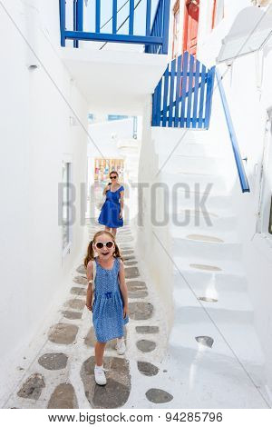 Family of mother and daughter at street of typical greek traditional village with white walls and colorful doors, windows and balconies on Mykonos Island, Greece, Europe