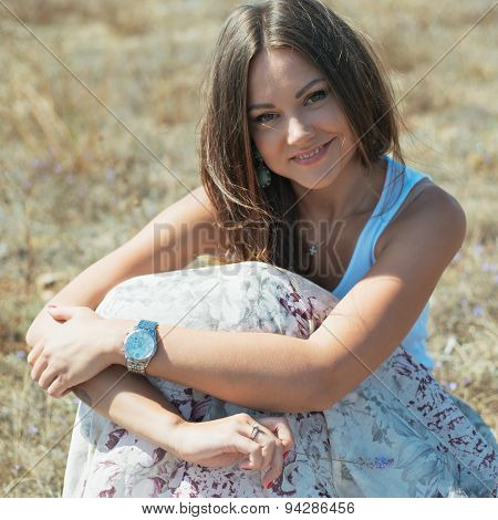 Beautiful Young Woman Which Sits On  Grass