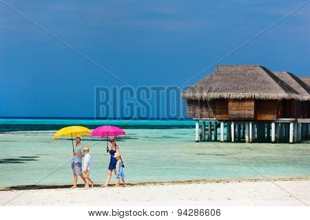 Beautiful family with colorful umbrellas walking along a beach on summer vacation
