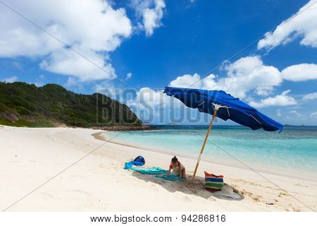 Little girl on picture perfect beach with blue umbrella, white sand, turquoise ocean water and blue sky at tropical island in Caribbean