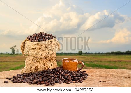 Coffee Beans In Burlap Sack On Wooden With Blurred Background