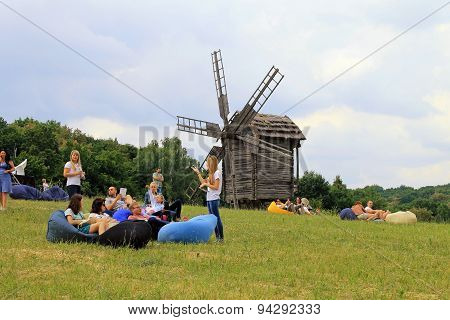 People Relax On Grass Near Old Wooden Mill In Museum Pirogovo, Kiev, Ukraine.