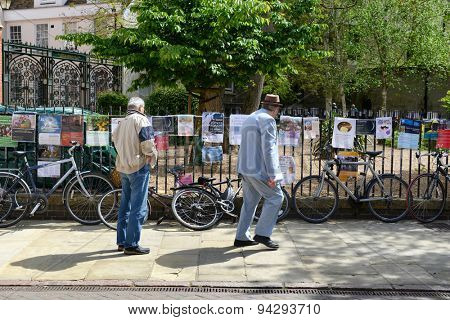 CAMBRIDGE, ENGLAND - MAY 13: People walking along the sidewalk reading advertising posters strung along a wrought iron railing above a row of bicycles in Cambridge, UK on a sunny day on May 13, 2015