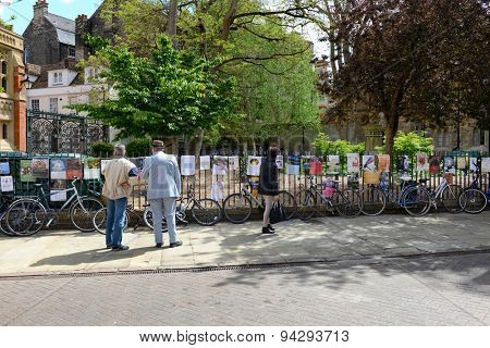 CAMBRIDGE, ENGLAND - MAY 13: Street scene in Cambridge, England with two men pausing on the pavement to read advertising posters on a wrought iron railing above a row of parked bicycles, May 13, 2015