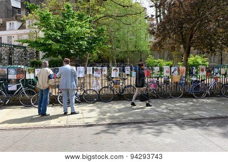 CAMBRIDGE, ENGLAND - MAY 13: Two men standing on the sidewalk reading advertising posters in Cambridge that have been mounted along a wrought iron railing above a row of parked bicycles, May 13, 2015