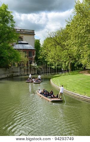 CAMBRIDGE, ENGLAND - MAY 13: People punting on the river in Cambridge rowing away from the camera around a bend in the river past historical buildings amongst lush green trees on May 13, 2015