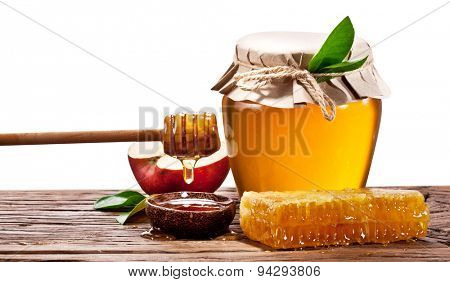 Glass cans full of honey, apples and honeycombs on wood. Clipping paths.