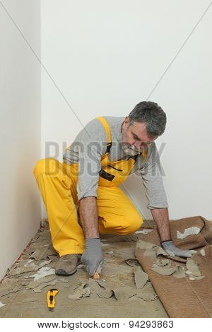 Worker Using Putty Knife For Cleaning Floor