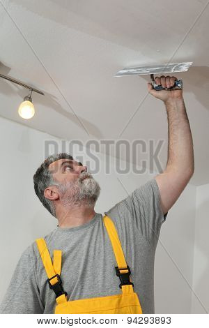 Home Renovation, Worker Repairing Plaster At Ceiling