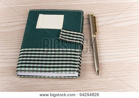 Notepad In With Clip And Metallic Pen On Table