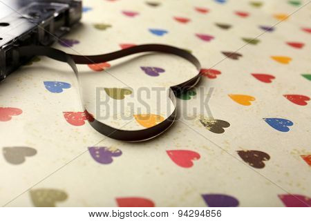 Audio cassette with magnetic tape in shape of heart on paper background