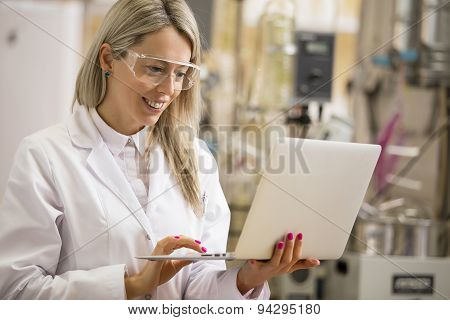 Female chemist working with laptop computer in the lab