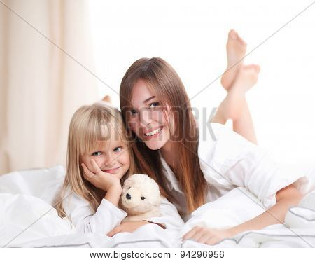 Woman and young girl lying in bed smiling.