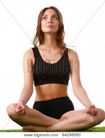 Young woman practicing yoga in the lotus position .
