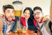 foto of dispenser  - Happy friends taking selfie with funny tongue out near beer tower dispenser  - JPG