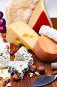 stock photo of dry fruit  - Cheeses with dried fruits and nuts on wooden board - JPG