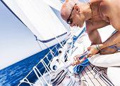 foto of work crew  - Handsome man working on sailboat - JPG