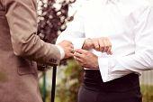 stock photo of cuff  - Capture of groomsmen helping Putting on cuff - JPG