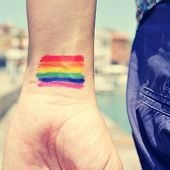 image of wrist  - closeup of a young man seen from behind with a rainbow flag painted in his wrist - JPG