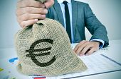 stock photo of greedy  - a young man wearing a gray suit seated at an office desk full of charts and financial balances holds a burlap money bag with the euro currency sign in his hand - JPG
