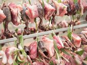 stock photo of spit-roast  - birds on the spit with meat bacon and sage ready for roasting - JPG