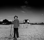 foto of combine  - Old farmer with hat and hayfork standing on field during harvest combine harvester in background black and white image - JPG