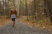 picture of woman boots  - Unrecognizable caucasian lonely woman with brown leather jacket and boots walking away in a jungle path in Autumn - JPG